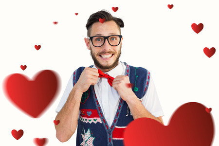 tightening: Geeky hipster wearing christmas vest against hearts Stock Photo