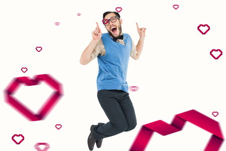 geeky: Geeky hipster jumping and smiling against hearts Stock Photo