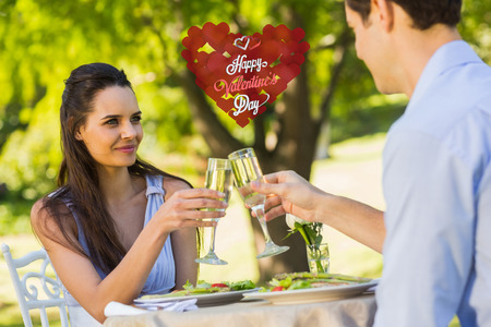 champagne flutes: Couple toasting champagne flutes at an outdoor café against cute valentines message