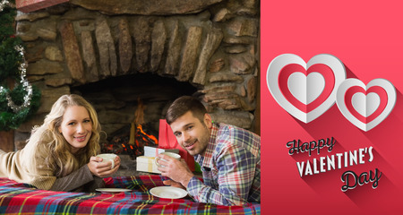 couple lit: Couple with tea cups in front of lit fireplace against happy valentines day Stock Photo