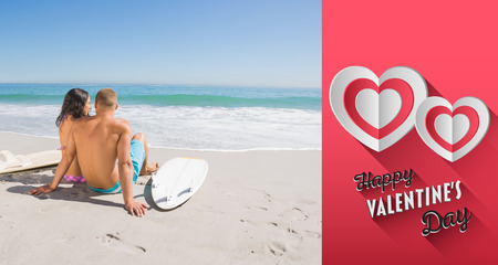 Pretty young couple with their surfboards looking at the sea against happy valentines day photo