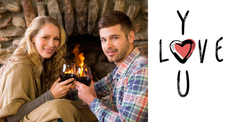 couple lit: Romantic couple toasting wineglasses in front of lit fireplace against cute valentines message