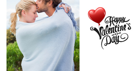 hair wrapped up: Cute affectionate couple standing outside wrapped in blanket against cute valentines message Stock Photo
