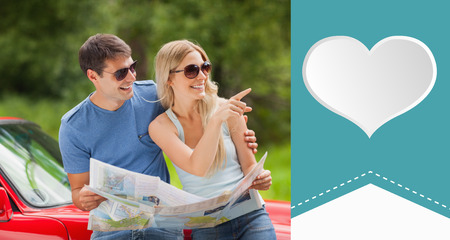 Cheerful young couple reading map against heart label photo