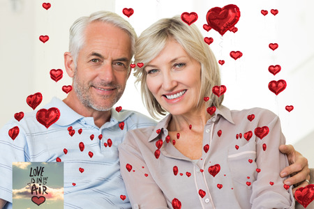arm around: Smiling mature couple sitting on sofa with arm around against love is in the air Stock Photo