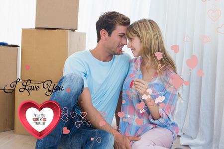 Couple holding new house key against cardboard boxes against cute valentines message photo