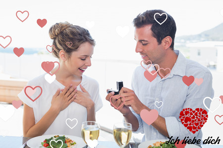 Liebe: Man surprising woman with a wedding ring at lunch table against ich liebe dich
