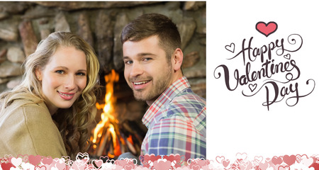 couple lit: Smiling young couple in front of lit fireplace against happy valentines day