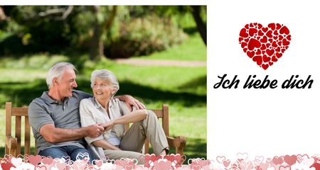 Liebe: Senior couple sitting on a bench against ich liebe dich