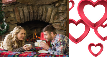 keeping room: Couple with tea cups in front of lit fireplace against pink hearts Stock Photo