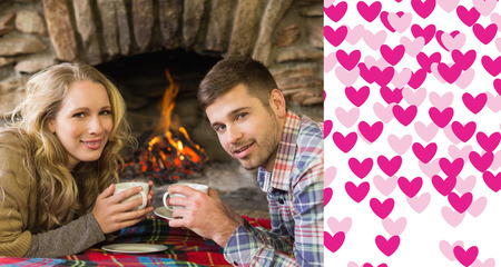 couple lit: Couple with tea cups in front of lit fireplace against valentines day pattern