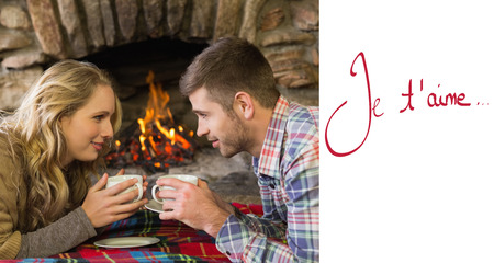 couple lit: Couple with tea cups in front of lit fireplace against valentines love hearts