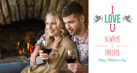 couple lit: Couple with wineglasses in front of lit fireplace against cute valentines message