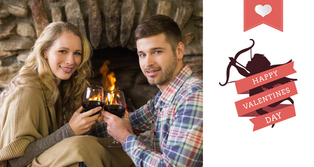 couple lit: Romantic couple toasting wineglasses in front of lit fireplace against happy valentines day Stock Photo