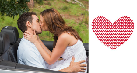 Beautiful couple kissing in back seat against valentines day pattern photo