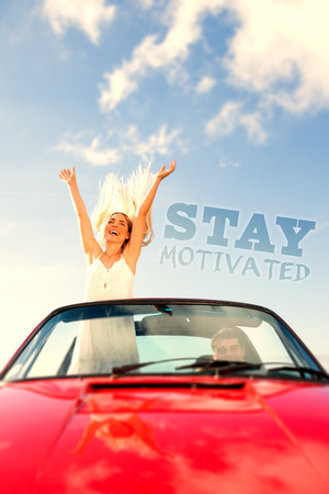 motivated: Happy woman standing in cabriolet while her boyfriend driving against stay motivated Stock Photo