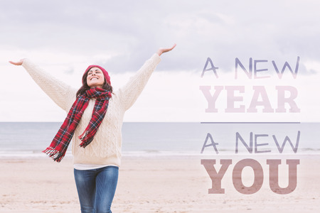 ropa casual: Mujer en ropa de abrigo que estira los brazos en la playa contra el nuevo año nuevo yo