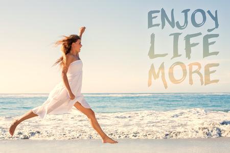 白いサンドレスに対してビーチにジャンプ アップで美しいブロンドは、もっと人生を楽しむ