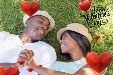 Happy couple lying in garden together on the grass against cute valentines message Imagens