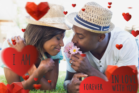 Happy couple lying in garden together smelling flowers against valentines message Imagens
