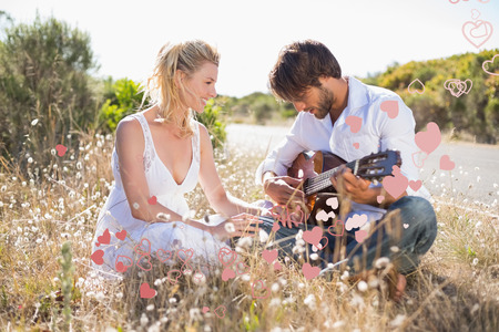 serenading: Handsome man serenading his girlfriend with guitar against valentines heart design