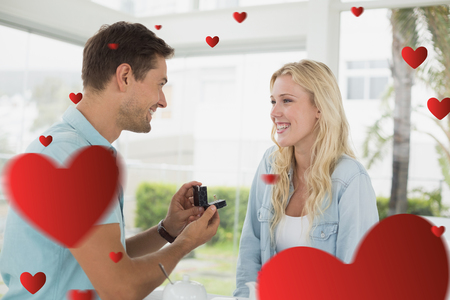 proposing: Man proposing marriage to his blonde girlfriend against hearts