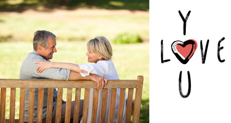 Happy retired couple sitting on the bench against cute valentines message photo