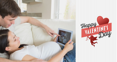 Prospective parents looking at ultrasound scan on tablet pc against happy valentines day photo