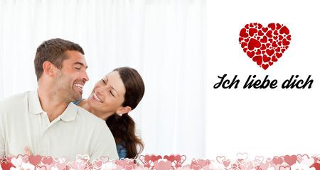 in liebe: Lovely couple laughing together in the living room against ich liebe dich