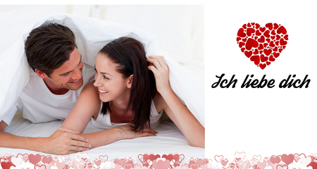 in liebe: Couple talking together and lying on bed against ich liebe dich Stock Photo