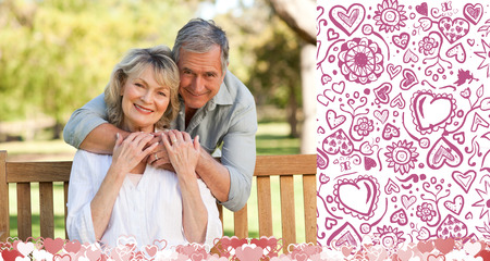 Elderly man hugging his wife who is on the bench against valentines pattern photo