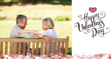 Happy retired couple sitting on the bench against happy valentines day photo
