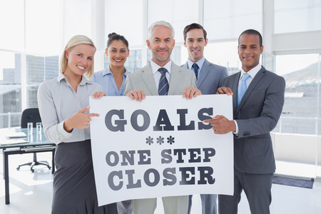 Business team holding large blank poster and pointing to it against goals one step closer photo