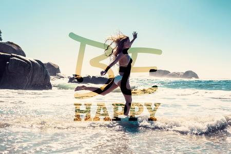 Mooie glimlachende vrouw in witte bikini overslaan op het strand tegen gelukkig zijn