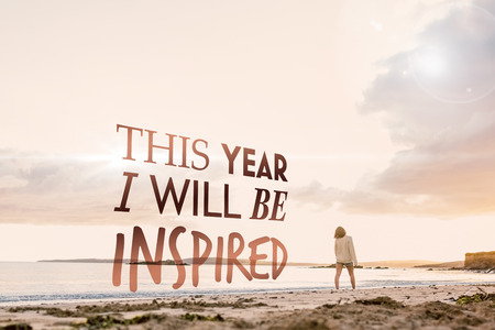 Woman in sweater walking on beach against i will be inspired