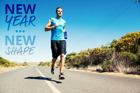 jogging: Athletic man jogging on open road holding bottle  against new year new shape