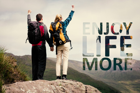healthy life: Excited couple reaching the top of their hike and cheering against enjoy life more