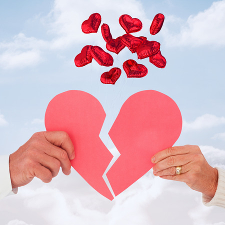 Couple holding a broken paper heart against cloudy sky photo