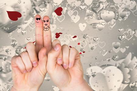 fingers crossed: Fingers crossed like a couple against love heart pattern