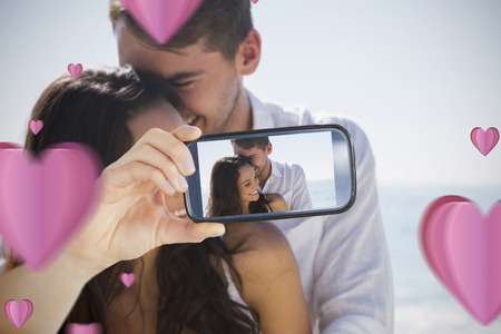 Composite image of valentines couple taking a selfie photo