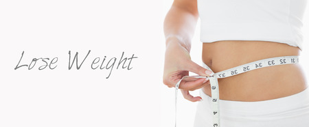 woman measuring waist: Closeup midsection of woman measuring waist over white background Stock Photo
