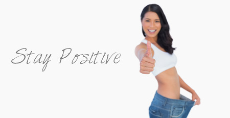 Victorious woman holding her too big pants thumbs up on white background photo