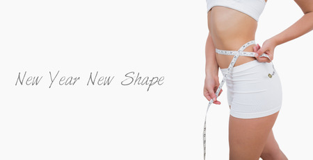 woman measuring waist: Midsection of fit woman measuring waist over white background Stock Photo
