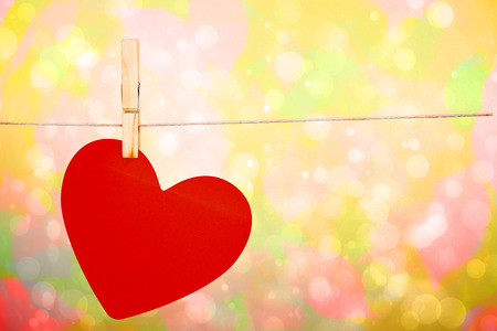 girly: Heart hanging on line against girly pink and yellow pattern