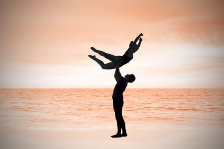beach scene: Ballet partners dancing gracefully together against beach scene Stock Photo