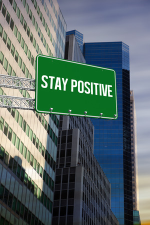 stay in the green: The word stay positive and green billboard sign against low angle view of skyscrapers Stock Photo