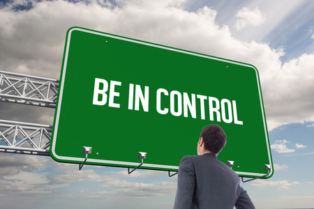 be dressed in: The word be in control and businessman standing with hand on hip against sky