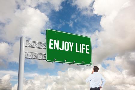 enjoy life: La parola godersi la vita e il pensiero d'affari che tocca il suo mento contro il cielo blu con nuvole bianche