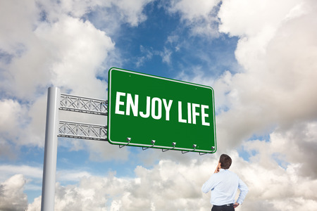 enjoy life: The word enjoy life and thinking businessman touching his chin against blue sky with white clouds