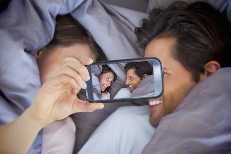 hair wrapped up: Composite of Couple taking selfie on smartphone